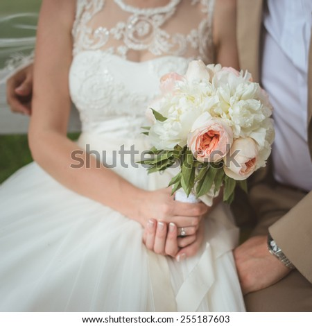 Beautiful wedding bouquet of white and pink  paeonies in hands of the bride - stock photo