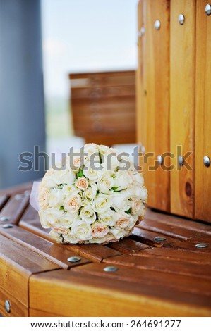 Beautiful wedding bouquet of white roses lying on a bench. - stock photo