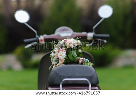 Beautiful wedding bouquet on scooters. Back view. Green lawn in the background - stock photo