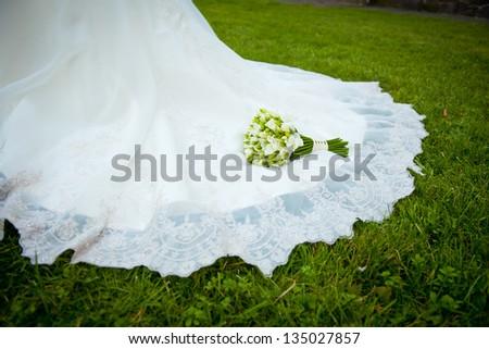 beautiful wedding bouquet which lies on a wedding dress - stock photo