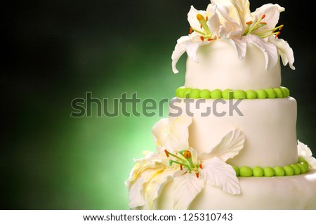 beautiful wedding cake on a green background - stock photo