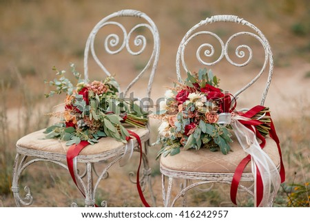Beautiful wedding colorful bouquets for bride on retro chairs in forest. Beauty of colored flowers. Bridal accessories. Female decoration for girl. Details for marriage and for married couple - stock photo