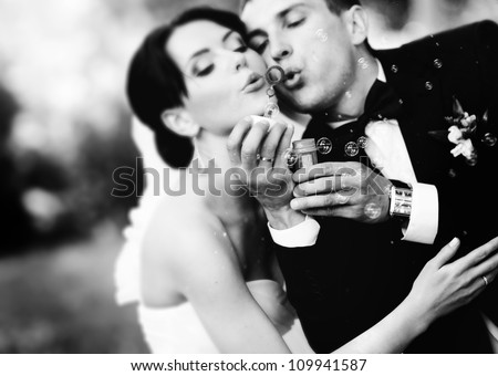beautiful wedding couple blowing bubbles - stock photo