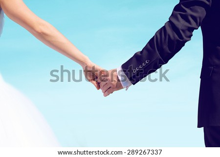 Beautiful wedding couple, bride and groom holding hands looking into a bright future over blue sky background - stock photo
