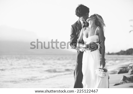 Beautiful Wedding Couple, Bride and Groom Kissing on the Beach at Sunset. Black and White Photograph - stock photo