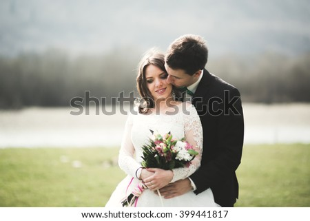 Beautiful wedding couple, bride, groom posing and walking in field against the background of high mountains - stock photo