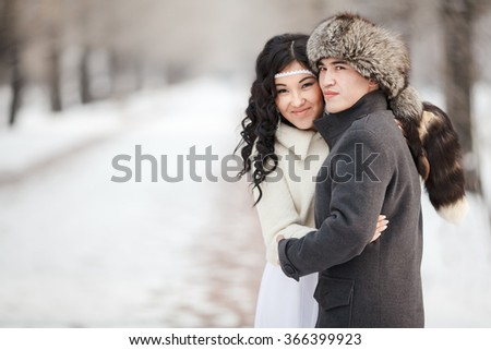 Beautiful wedding couple, exotic asian bride and groom embraced. Young man in winter coat and fur hat, bride in white wedding dress with sheepskin veil. Cold season warm clothing, copy space for text. - stock photo