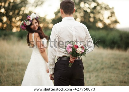 Beautiful wedding couple in park. kiss and hug each other - stock photo