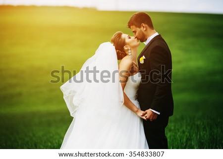 Beautiful wedding couple is walking on the green field - stock photo