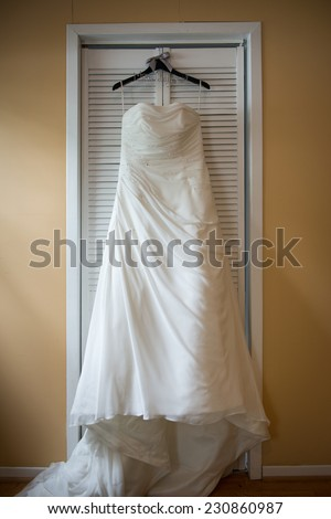 Beautiful wedding dress on hanger, in natural light from window - stock photo