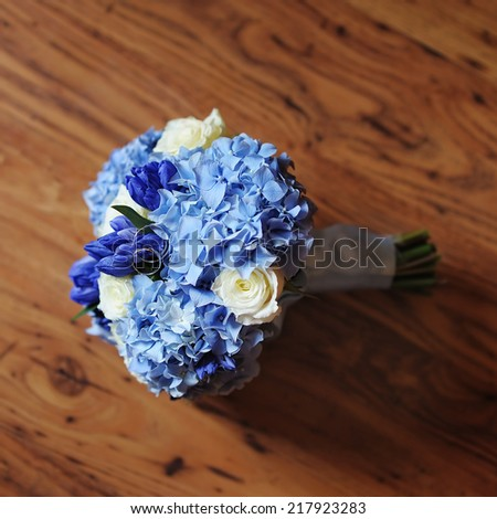 Beautiful wedding flowers bouquet and wedding rings on the wooden dark background - stock photo