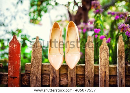 beautiful wedding shoes hanging on a fence - stock photo