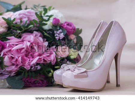 Beautiful wedding shoes with high heels and a bouquet of colorful flowers hydrangea, peonies and roses on a background of kraft paper, decorations, preparing for the wedding, details, boudoir - stock photo