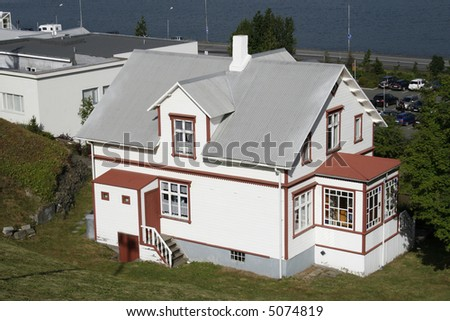 beautiful white and red wooden mansion with grey roof at lake front - stock photo