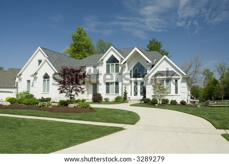 Beautiful white brick home featuring a very modern architectural design with large windows and beautiful  landscaping. - stock photo