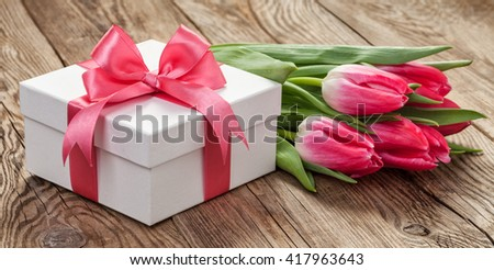 beautiful white gift box with tulips on old wooden boards. - stock photo