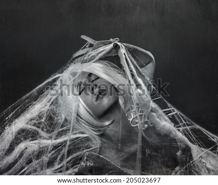 beautiful white-haired woman caught in a spider web - stock photo