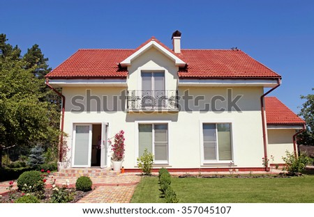 Beautiful white house with green lawn and blue sky - stock photo