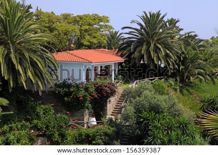 Beautiful white house with red tile roof, small terrace and steps in the mediterranean garden(Greece).  - stock photo