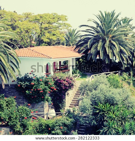 Beautiful white house with red tile roof, small terrace and steps in the mediterranean garden, Greece. Square toned image, instagram effect - stock photo