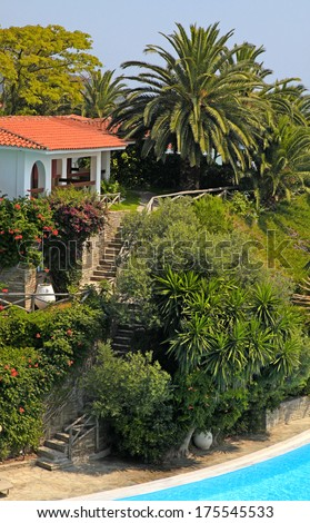 Beautiful white house with red tile roof, steps and swimming pool in the mediterranean garden(Greece).   - stock photo
