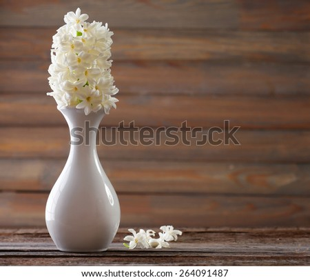 Beautiful white hyacinth flower in vase on table on wooden background - stock photo