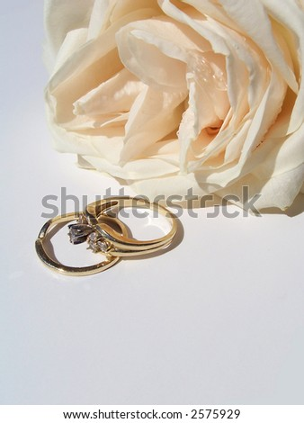 Beautiful white rose with dew drops and engagement ring over white background .Perfect image for event projects : marriage proposal , anniversary and Valentine's day . - stock photo