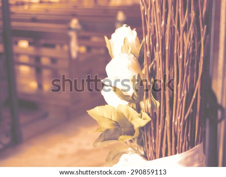 Beautiful white roses  wedding decoration in the church. Retro aged photo. Blurred image with soft focus. - stock photo