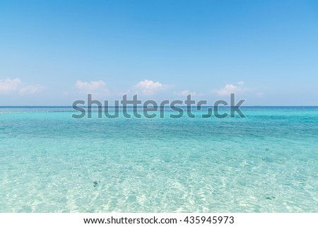 Beautiful white sand on Tropical beach blue water and blue sky - stock photo