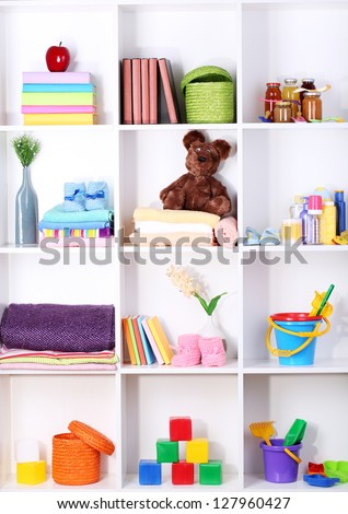 Beautiful white shelves with different baby related objects - stock photo