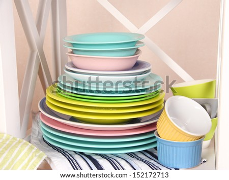 Beautiful white shelves with tableware and decor, on color wall background, close-up - stock photo