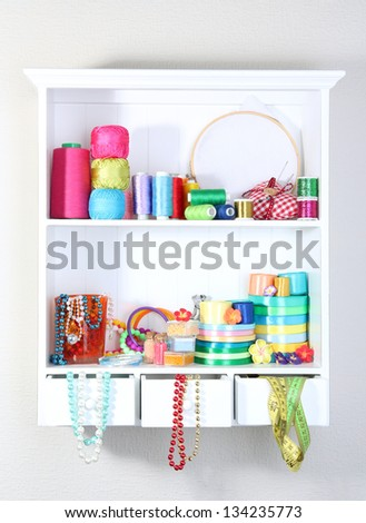 Beautiful white shelves with thread and material for handicrafts - stock photo