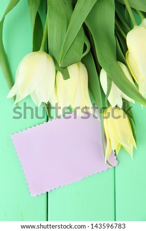Beautiful white tulips on color wooden background - stock photo
