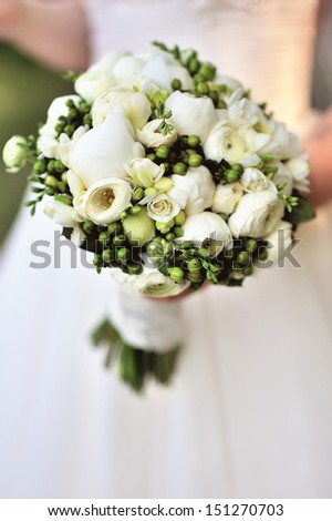 Beautiful white wedding bouquet in hand of bride - stock photo