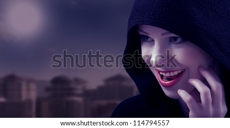 beautiful wicked witch in a black hood on the day of Halloween - stock photo