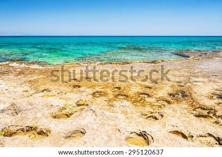 Beautiful wild beach with clear turquoise water and rocks. Malia, Crete island, Greece. Selective focus - stock photo