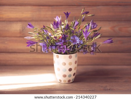 Beautiful wild flowers in vase on wooden background - stock photo
