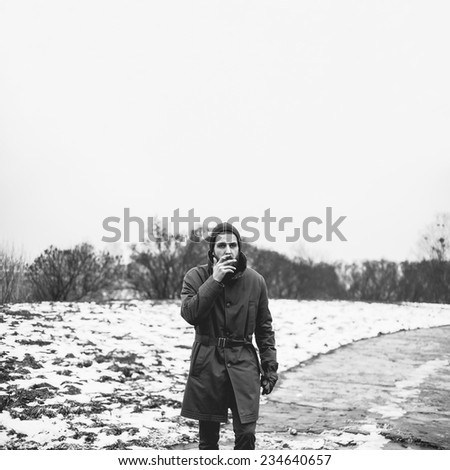 Beautiful winter brutal man with a cigarette - stock photo