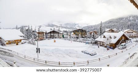 Beautiful winter day in the Italian mountain village near Dolomite cliffs. A lot of snow. - stock photo