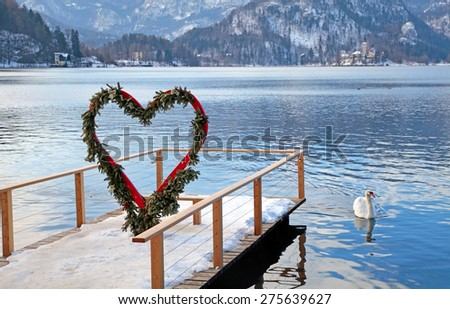 Beautiful winter landscape with pier and heart arch, Lake Bled, Slovenia. Selective focus - stock photo