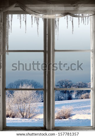 Beautiful winter landscape with rime frost in bushes and trees, seen through an old window with icicles - stock photo