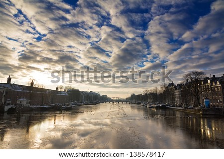 Beautiful winter panorama of the river Amstel in Amsterdam, the Netherlands, looking towards the skinny bridge. - stock photo