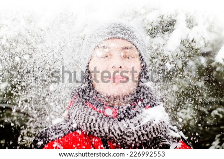 Beautiful winter portrait of young woman with snow falling on her face in the winter snowy scenery - stock photo