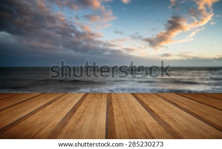 Beautiful Winter sunset sky over long exposure waves in ocean with wooden planks floor - stock photo
