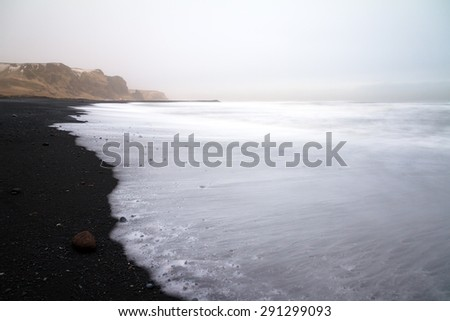 Beautiful winter view of the black sand and rough sea at the beach of Vik in Iceland - stock photo