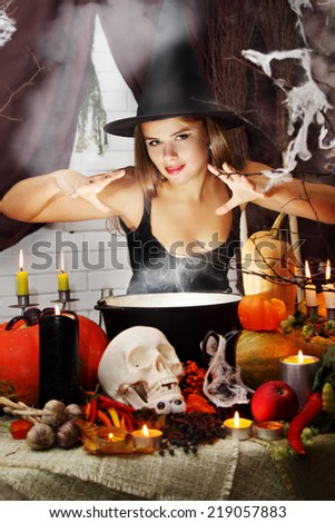 beautiful Witch brew the potion in the boiler - stock photo