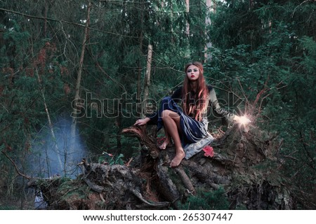 beautiful witch in forest - stock photo