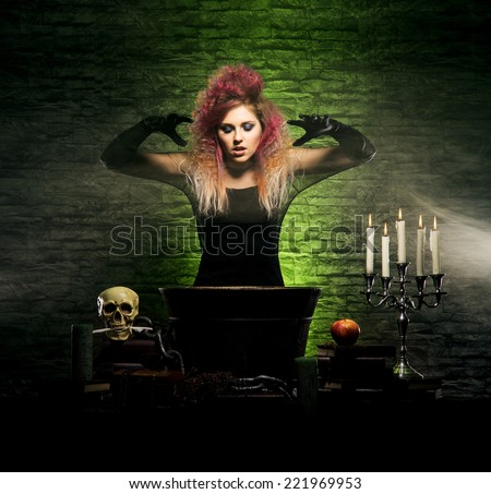 Beautiful witch making the witchcraft over the smoky background. Halloween image - stock photo