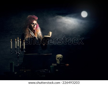 Beautiful witch making the witchcraft over the smoky background. Halloween image. - stock photo