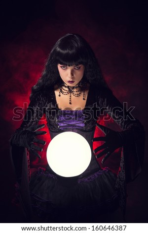 Beautiful witch or fortune teller with a crystal ball, studio shot over smoky background  - stock photo